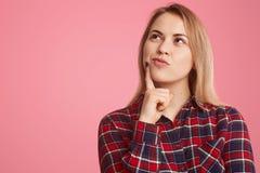 Innenschuß der durchdachten jungen Frau hält Vorderfinger nahe dem Kinn, oben fokussiert, Tagträume über etwas, trägt kariertes H lizenzfreies stockfoto