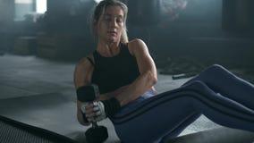 Innenschuß der Eignungsfrau arbeitet an der Turnhalle aus Muskulöse junge Frau, die Übungs-ABS mit Dummköpfen an tut stock video footage