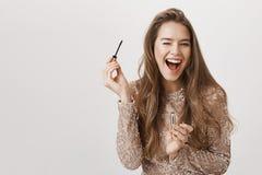 Innenschuß der positiven attraktiven kaukasischen Frau, die breit beim Halten der Wimperntusche und Anwenden sie blinzelt und läc Lizenzfreie Stockbilder