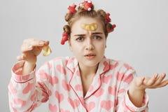 Innenschuß des ahnungslosen verwirrten weiblichen Mädchens in den Haarlockenwicklern und in den Pyjamas, Augenklappemaske auf Sti lizenzfreie stockbilder