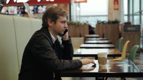 Innenschuß des lächelnden jungen Mannes, der an der Kaffeestube sitzt und am Handy spricht Glücklicher junger Kerl am Café, das a stock video
