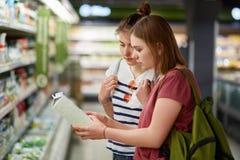 Innenschuß von zwei jungen weiblichen Begleitern kommen in Speicher für das Kaufen von notwendigen Produkten, halten Milch, vergl Stockbild