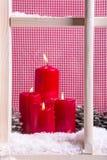 Innenweihnachtsfensterbrettdekoration:  vier rote Kerzen, Schnee Lizenzfreie Stockfotografie