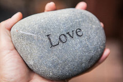 Inner balance concept: hands holding stones with the word love. Hands holding pebble stones with the word love Royalty Free Stock Image