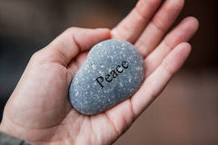 Inner balance concept: hands holding stones with the word peace Royalty Free Stock Photos