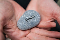 Inner balance concept: hands holding stones with the word peace Royalty Free Stock Images