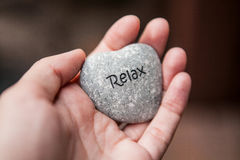 Inner balance concept: hands holding stones with the word relax. Hands holding pebble stones with the word relax Stock Image