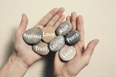 Inner balance concept: hands holding stones with the words happi. Inner balance concept: hands holding stones with text for happiness, love, trust, courage, hope Royalty Free Stock Photos