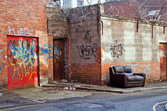 Inner city dereliction. Abandoned couch in inner city graffiti covered alleyway stock photography