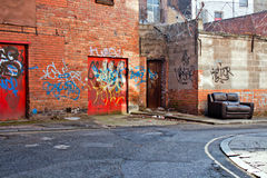 Inner city dereliction. Abandoned couch in inner city graffiti covered alleyway stock images