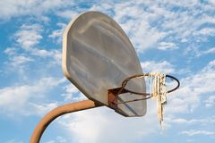 Inner City Urban Basketball. Vandalized, rusty urban basketball hoop, net, stanchion and backboard, shot against a brilliant blue sky stock photography