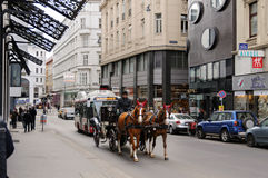 Inner city. Vienna, Austria. Traditional horse riding in a Fiaker through the city center.  Lichtensteg-street, Vienna, Austria Royalty Free Stock Image