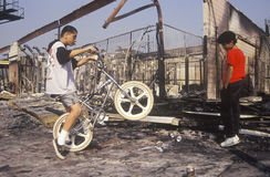 Inner city youth riding bicycle at burned out buil Stock Photos