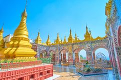 The inner courtyard with pagodas, Mandalay Hill temple, Myanmar. The wall patterns, performed in mirror work technique are the visit card of Su Taung Pyae Temple royalty free stock photos