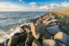 The polder dike with stone bollards along the Ijsselmeer at Flev. An inner lake in the Netherlands with waves striking on the stone dykes of the polder during Royalty Free Stock Photo