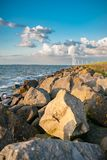The polder dike with stone bollards along the Ijsselmeer at Flev. An inner lake in the Netherlands with waves striking on the stone dykes of the polder during Stock Photos