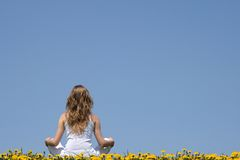 Inner peace. Longhaired young woman in white clothes sitting in a flowering dandelion field Stock Image