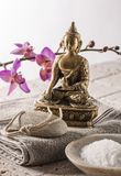 Inner peace for inner beauty. Bronze Buddha set on cotton towel with footcare and skin exfoliation accessories on limestone background for relaxation and Stock Images