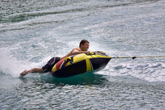 Inner tube fun. Man laying on inner tube being pulled by a fast boat Stock Images