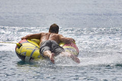 Inner tubing fun. Man riding on an inner tube being pulled by a fast boat Stock Photo