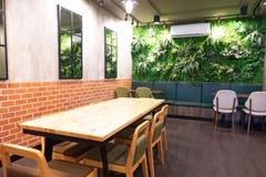 Innerer moderner Raumholztisch und Stühle und Baum an der Wand stockfoto