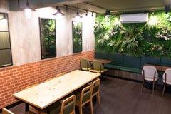 Innerer moderner Raumholztisch und Stühle und Baum an der Wand lizenzfreies stockfoto