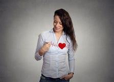 Innerer Schlag Frau, die ein Herz auf ihrem Hemd zeichnet Stockbild