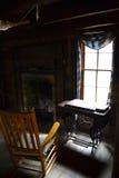 Inneres Blockhaus mit Schaukelstuhl durch Fenster Stockfoto