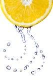 Inneres vom Wasser fällt auf die Zitrone, die auf Weiß getrennt wird Lizenzfreies Stockbild