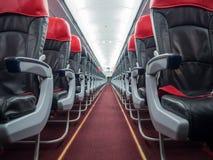 Innerhalb der Passagierflugzeugkabine einzelner Gang, Wirtschaftssitz Lizenzfreies Stockbild