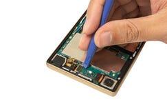 Innerhalb der Rückseite des Smartphone und benutzt ein Reparaturwerkzeug stockbild