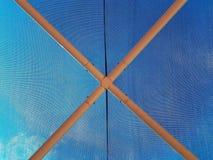 Innerhalb des blauen Geweberegenschirmes stockbilder