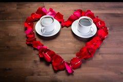 Innerhalb des Herzens der rosafarbenen Blumenblätter sind zwei Tasse Kaffees Lizenzfreies Stockfoto