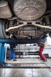 Innerhalb einer Garage - zwei Mechaniker, die an einem Auto arbeiten Stockfotografie