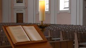 Innerhalb einer leeren katholischen Kirche Hölzerne Bänke für Kirchenmitglieder und das Gebetsbuch des Priesters stock video