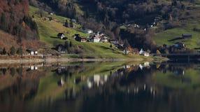 Innerthal, wenig Dorf in Schwyz-Bezirk, der im See Wagital widerspiegelt Stockbilder