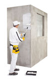 Innesco del lavoratore con una parete del cemento del rullo di pittura Fotografia Stock