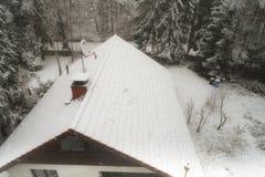 Innevato, tetto, di una villetta in una foresta con un'antenna satellitare innevata ed i pini al bordo fotografie stock
