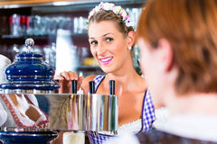 Innkeeper in Bavarian pub with customers royalty free stock photos