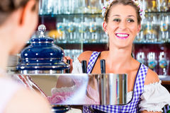 Innkeeper in Bavarian pub with customers stock images