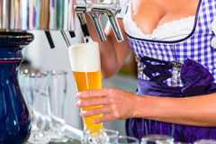 Innkeeper in pub drawing beer Stock Photo