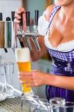 Innkeeper in pub drawing beer Royalty Free Stock Photos
