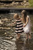 Innocence, purity and youth concept. Girls walk on stones in water stream at waterfall. Children play on sunny summer day on natural landscape Stock Image