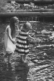 Innocence, purity and youth concept. Girls walk on stones in water stream at waterfall. Children play on sunny summer day on natural landscape Stock Images