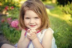 Innocence, purity and youth concept. Future and flourishing. Girl smiling with folded hands in summer garden. Child sitting at blossoming rose flowers on green Royalty Free Stock Image