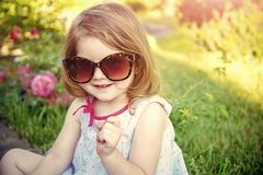 Innocence, purity and youth. Girl in sunglasses sitting in park on floral environment. Child smiling with raised finger in summer garden. Summer vacation and Stock Images