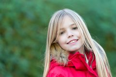 Innocence, purity and youth. Girl with blond long hair smile on natural environment. Happy childhood concept. Beauty, nature, growth. Child in red coat enjoy Royalty Free Stock Photography