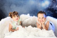 Innocent. Beautiful little angels at a snowy background Royalty Free Stock Photography