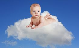 Innocent baby. Baby boy situated on a cloud with a blue sky background Stock Images
