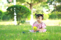 Innocent baby girl play a ball on the lawn. Carefree Chinese little baby girl, sit on a lawn, play with leaves, enjoy free time, embrace nature, beautiful summer Royalty Free Stock Photos